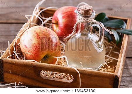 Close up image of a bottle of unfiltered apple cider vinegar and apples in a wooden box over rustic background