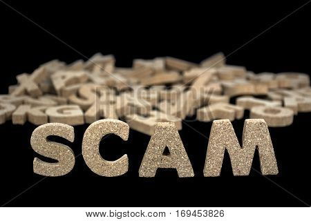 word scam in cork block letters on black