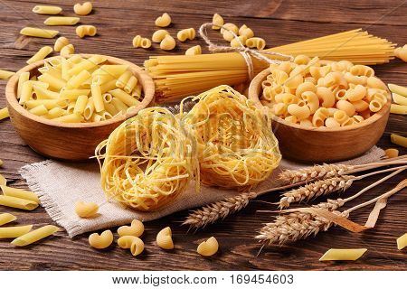 Pasta of different types in a wooden bowl and scattered on the surface of the table