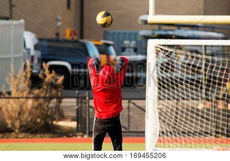 A track and field athlete throws a medicine ball backwords during practice