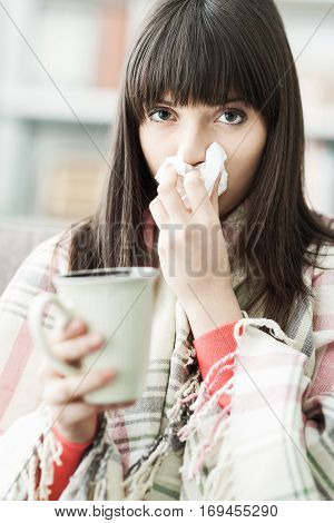 Sick woman at home having cold and flu she is blowing her nose and having an hot drink