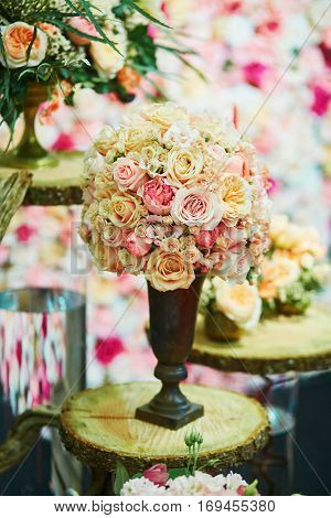 Elegant table set with huge bucket of pink roses for an event party or wedding reception