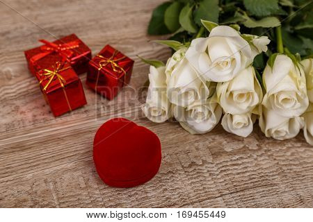 Roses with heart engagement box. Love design on wood background. Valentines day concept. Fresh natural flowers with gift boxes. Wooden rustic board.