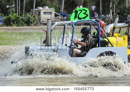 Naples Florida USA - March 3 2012: Swamp buggy plowing mud in shallow section of course