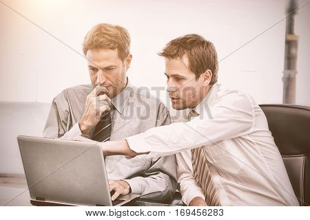 Two handsome businessmen working together on a project sitting at a table in the office