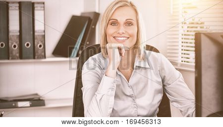 Smiling woman with chin on hand behind a desk inan office