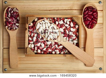 Wooden box with haricot beans and spoons, closeup