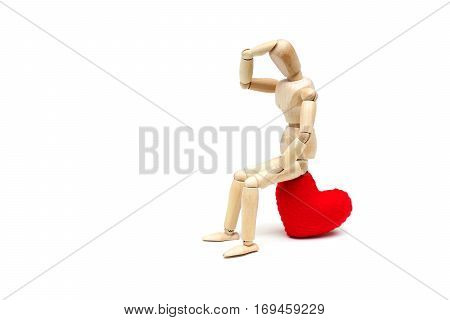 Wood Figure Mannequin sitting sadly on a red heart waiting for love