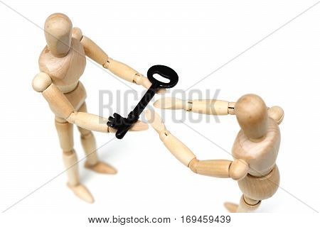 Wood Figure Mannequin giving a key to the other person / Business success concept