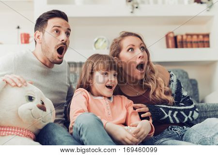 Family watching scary movie at home together.