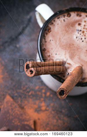 Vintage mug of hot chocolate with cinnamon sticks over dark background. Focus on cinnamon. Top view.