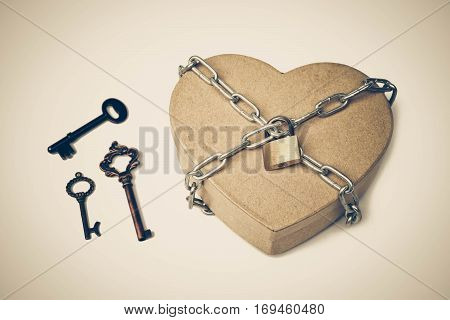 A heart shape box chained with three different types of old keys / Keys for love concept