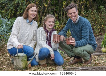 Attractive, successful and happy family, man, woman, girl child, mother, father and daughter gardening together in a garden vegetable patch