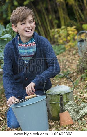 Happy smiling male boy child gardening with bucket, garden fork and watering can in a vegetable patch