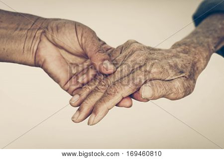 Elderly people holding hands together isolated in vintage tone
