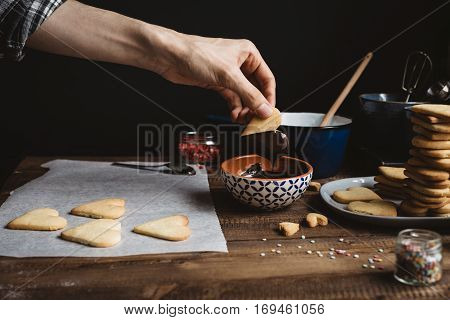 Male Dipping Heart Shaped Biscuit in Bowl of Melted Chocolate
