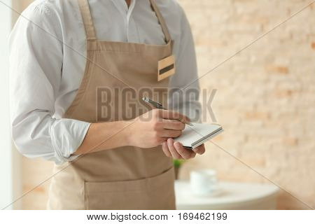 Waiter in beige apron writing down an order in a cafe, close up