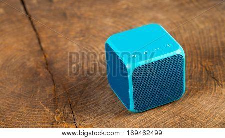 Blue speaker cube on wood background isolated