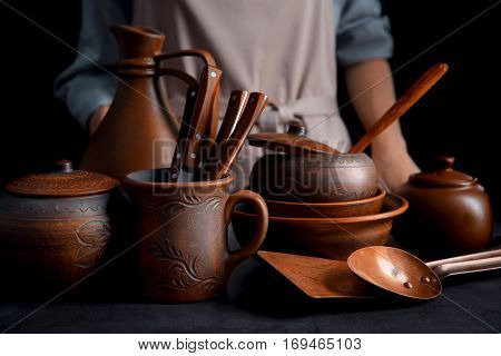Brown dishware and woman on dark background