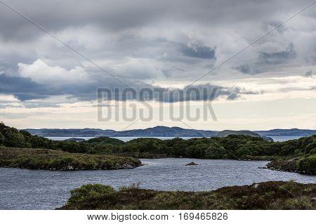 Northwest Coast Scotland - June 6 2012: Wide landscape of Loch A Chaim Bhaim irregular coastline under gray clouds. Green rocky rock formations in water upfront. Horizon of mountains.