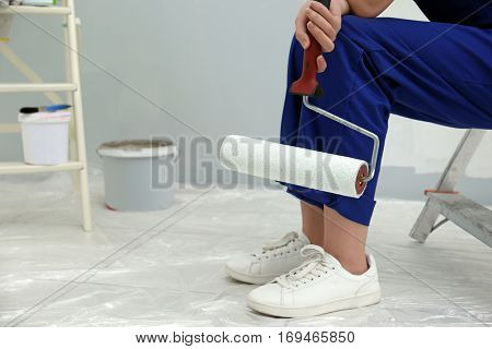 Young female decorator sitting on ladder in empty room, closeup