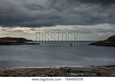 Northwest Coast Scotland - June 6 2012: Scourie Bay as part of the Atlantic Ocean in the evening during twilight. A sail boat returns to the harbor. Rocky shores and a cloudscape of rain. Far out light blue sky.