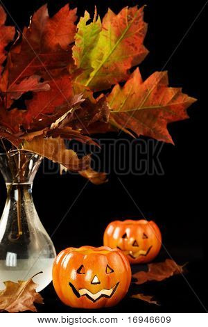 Autumn leaves and halloween pumpkins in the dark