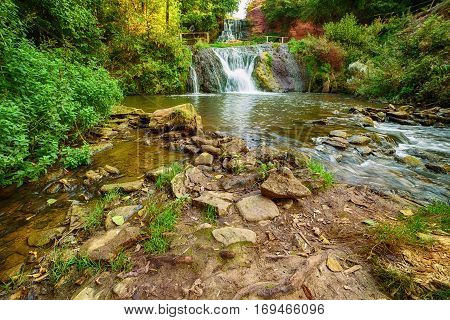 Beautiful mountain rainforest waterfall with fast flowing water and rocks, long exposure. Natural seasonal travel outdoor background