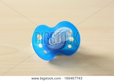Baby pacifier on wooden background