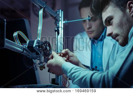 Engineering Team Working On A 3D Printer