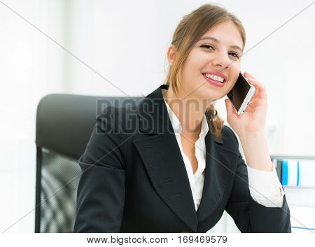 Smiling businesswoman talking on the phone in her office