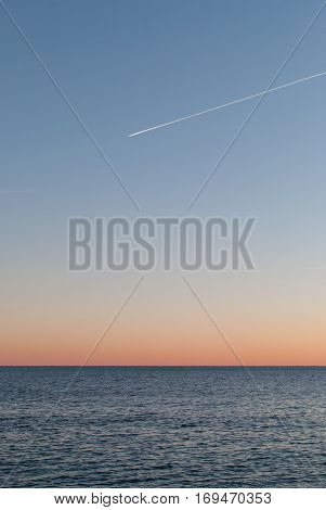 Open sea at sunset with colorful gradient sky background, horizon line splitting the photo in half