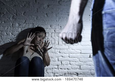 young couple in problems with drunk husband or man attacking and threatening wife or girl crying on the floor scared and terrified in domestic violence and cruel abuse of women