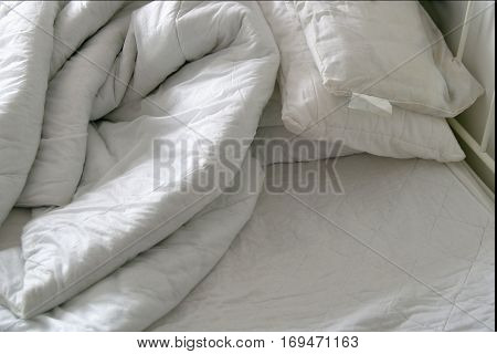 Duvet and pillows on an unmade bed