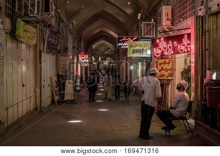 Picturesque photo of a covered street  of Isfahan bazaar with warm colors and iranians walking.