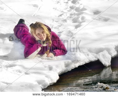 Girl with a scythe lies on the banks of the creek in the snow
