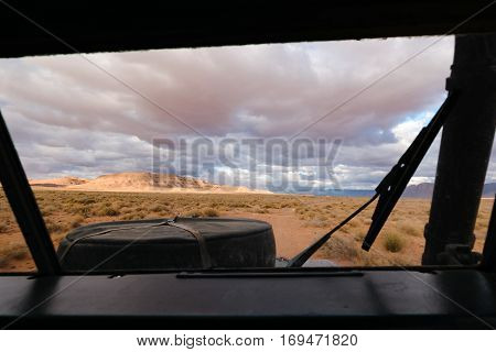View from the drivers position of an four by four oldtimer off-road vehicle driving off- road in a stone desert in Morocco. You can see the spare wheel on the hood.