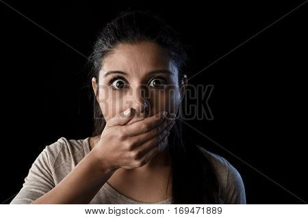 young beautiful scared Spanish woman in shock and surprise face expression covering her mouth astonished and amazed isolated on black background in primal facial emotion concept