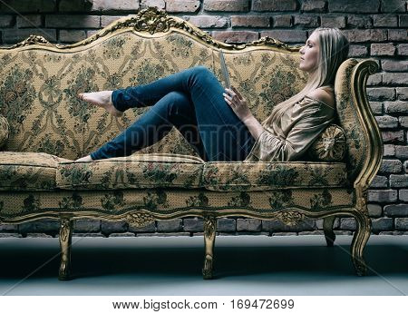 Young woman resting on baroque design sofa, using tablet computer. Side view.