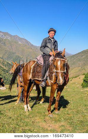 Boy On Brown Horse In Kyrgyzstan
