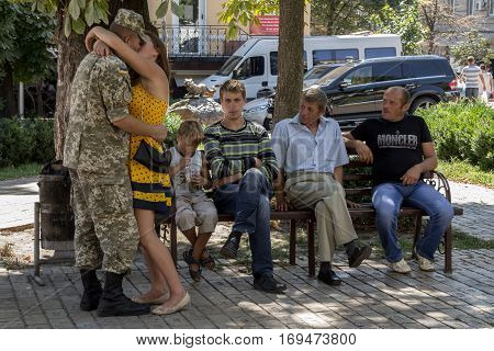KIEV UKRAINE - AUGUST 9 2015: Ukrainian soldier on leave from the Eastern Ukraine conflict kissing his girlfriend next to his relatives