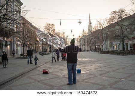 NOVI SAD SERBIA - DECEMBER 13 2015: Street performer making soap bubbles in order to amuse people passing by on Novi Sad main street Zmaj Jovina