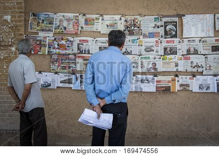 YAZD, IRAN - AUGUST 15, 2016: People reading Iranian newspapers hung on a wall
