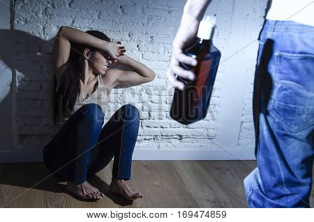 young couple in problems with drunk alcoholic husband or man attacking and threatening with bottle to wife or girl crying on the floor scared and terrified in domestic violence and cruel abuse of women