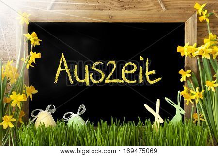 Blackboard With German Text Auszeit Means Downtime. Sunny Spring Flowers Nacissus Or Daffodil With Grass, Easter Egg And Bunny. Rustic Aged Wooden Background.
