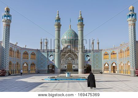 ARAN VA BIDGOL, IRAN - AUGUST 18, 2016: Aran va bidgol Mosque/holy shrine near Kashan Iran with a veiled woman walking in front of it. Aran va Bidgol is a city in and the capital of Aran va Bidgol County Isfahan Province Iran famous for its mosque and the