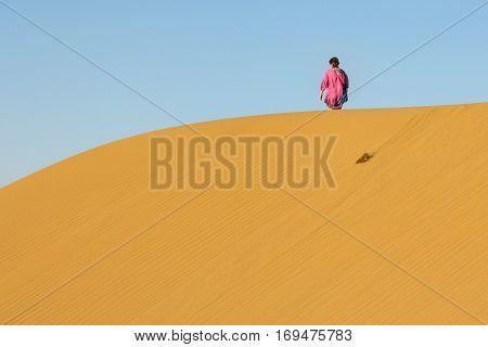 MARANJAB DESERT, iRAN, AUGUST 18, 2016: Woman walking on Sand dunes in the Maranjab desert near Kashan Iran