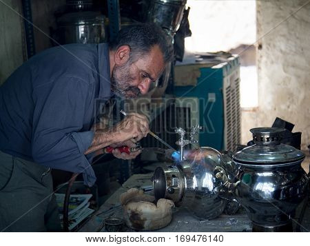 KASHAN IRAN - AUGUST 13 2016: Crafstman reparing a samovar in Kashan bazaar Iran Samovars (sometimes also spelled Samavar or Samaavar) are used to boil water for tea and are a staple in most Persian homes.