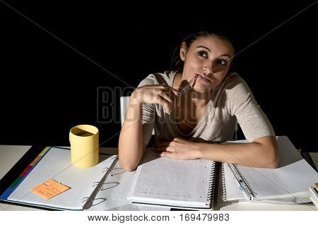 young beautiful Spanish girl studying tired and bored at home late night absent minded looking thoughtful and happy daydreaming in education stress concept