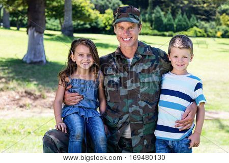 Happy soldier reunited with his son and daughter in the park on a sunny day